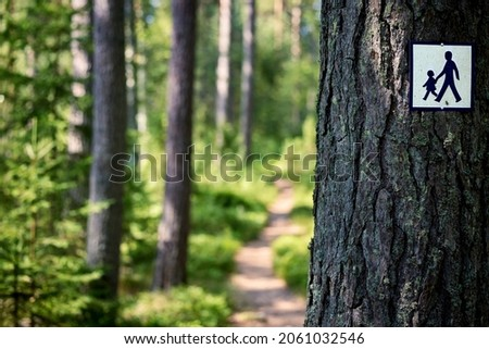Footpath in green forest with footpath symbol sign attached to tree trunk. Royalty-Free Stock Photo #2061032546