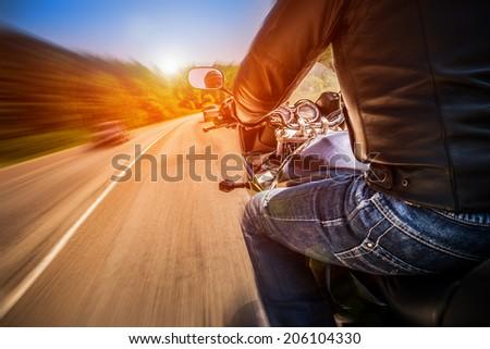 Biker driving a motorcycle rides along the asphalt road. #206104330