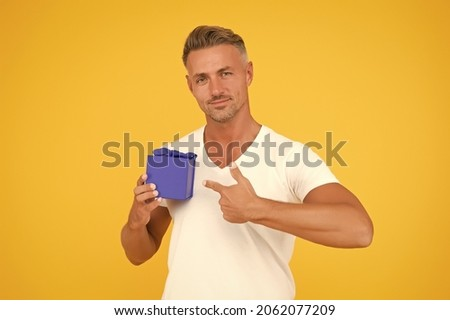 Romantic gift. Mature guy hold present box yellow background. Love romantic feelings concept. Happy birthday darling. Man happy face celebrate valentines day. Little gift. Gift for girlfriend Royalty-Free Stock Photo #2062077209