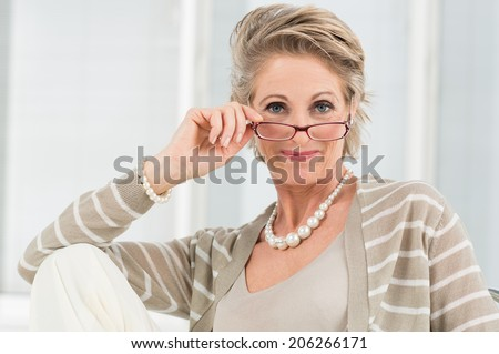 Portrait Of Happy Mature Woman Looking Through Glasses #206266171