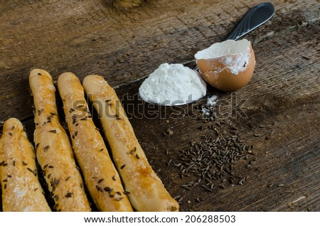 Homemade baked breadsticks on wood table with eggs #206288503