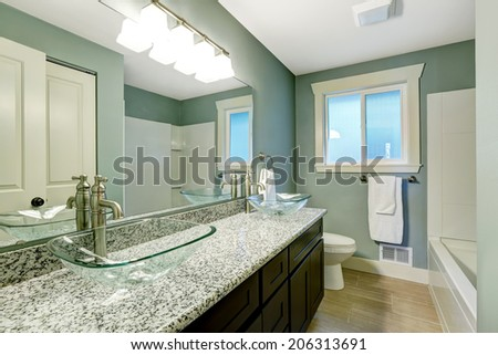 Modern bathroom interior with window. View of wooden vanity cabinet with granite counter top and glass vessel sinks #206313691