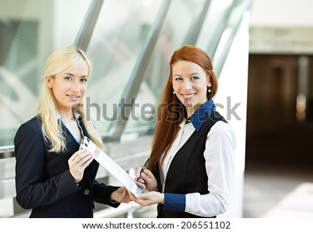 Closeup portrait two smiling young business women, company employees signing contract document, agreement paper, paperwork isolated corporate office background. Positive face expressions, emotions