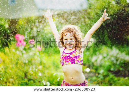 Little girl under water splashes in the summer garden. #206588923