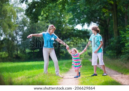 Happy active woman enjoying hiking with two children, school age boy and cute curly toddler girl walking together in a beautiful pine wood forest on a sunny summer day #206629864