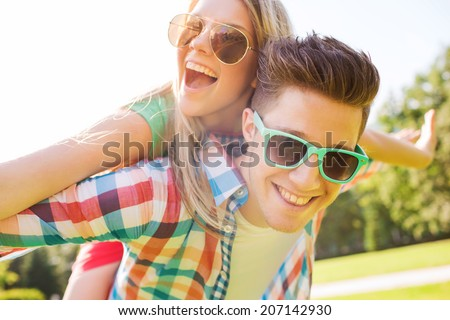 holidays, vacation, love and friendship concept - smiling couple having fun in park #207142930