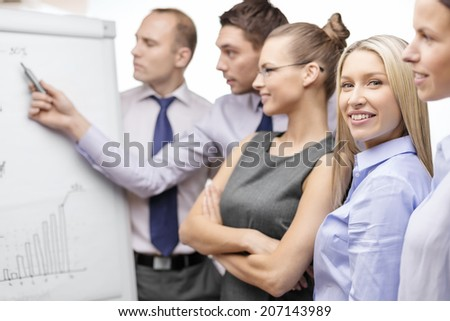 business and office concept - smiling business team with charts on flip board having discussion #207143989