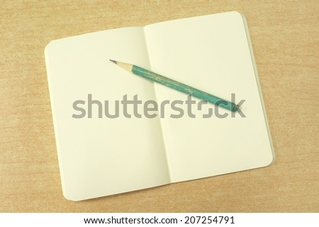 open notebook with blank pale yellow pages and old pencil on wooden desk #207254791