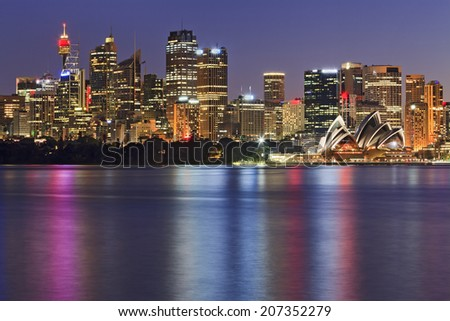 Australia Sydney city CBD view from cremorne point over harbour waters at sunset highly illuminated buildings and houses reflecting lights in blurred water