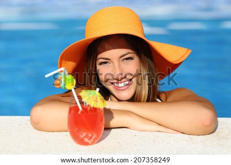 Beauty woman with perfect smile enjoying a cocktail in a swimming pool on vacations with blue water in the background