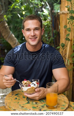Young fitted man enjoying an organic juice and cereals in a raw restaurant #207490537