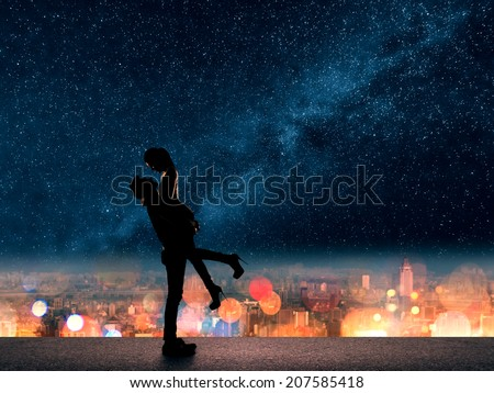 Silhouette of Asian couple, man hold his girlfriend up above the city in night under stars.