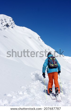 A skier going up in the mountains.  #207687787