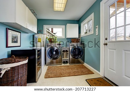Light blue laundry room with modern steel appliances and white cabinets