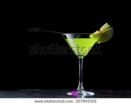 appletini cocktail with apples slices, vodka, pineapple juice, liqueur in classic martini cocktail glass #207842356