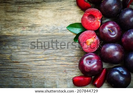 plums on a dark wood background. toning. selective focus on plum with a stone. #207844729
