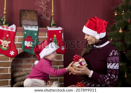 mother receives a gift from her baby near the fireplace and Christmas tree #207899011