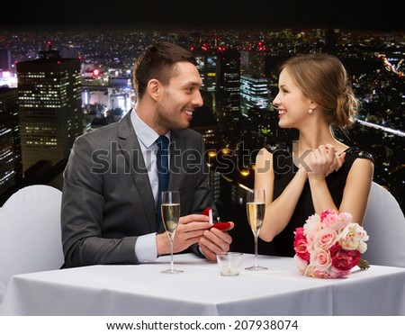 restaurant, couple and holiday concept - smiling man proposing to his girlfriend at restaurant #207938074