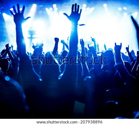 silhouettes of concert crowd in front of bright stage lights #207938896