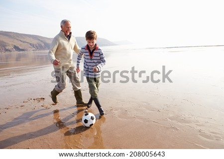 Grandfather And Grandson Playing Football On Winter Beach #208005643