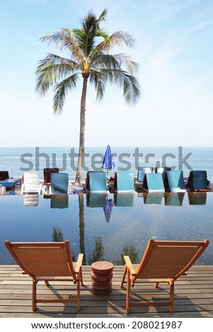 Great review for a luxury beachfront pool, the ocean and swaying palm trees. Two convenient comfortable guest sun loungers and a bedside table are worth on a wooden platform. Charming lookout for two #208021987