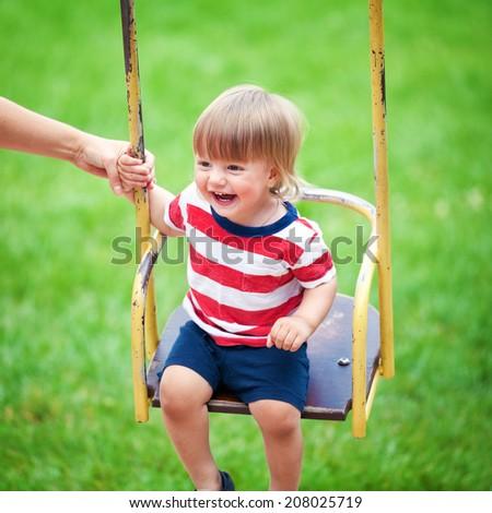 Happy little boy having fun on a swing outdoors #208025719