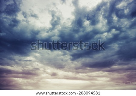 Dark blue stormy cloudy sky natural photo background with Instagram toned effect Royalty-Free Stock Photo #208094581