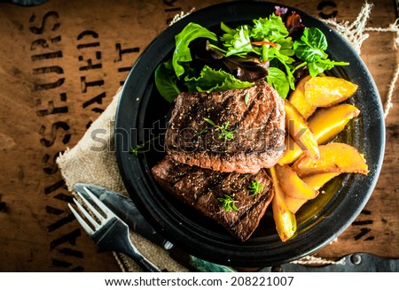 Overhead view of delicious,grilled beef steak with roasted pumpkin and fresh green herb salad on an old wooden packing case with printed text #208221007