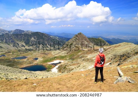 Beautiful mountain landscape with young woman standing and admiring the view #208246987