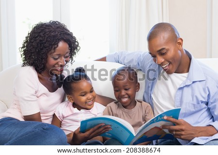Happy family on the couch reading storybook at home in the living room #208388674