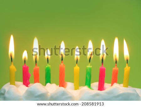 Ten lit brightly colored candles in a row in white icing with bright green background. Horizontal composition with copy space in upper part of image. Good for birthdays, anniversaries and milestones