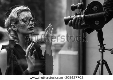 Elegant blond retro woman in black dress with camera