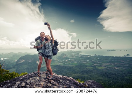 Couple of hikers taking photo of themselves on top of the mountain with green valley on the background