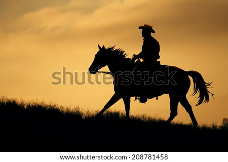 A cowboy silhouette riding on a mountain with an yellow sky.