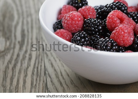 ripe blackberries and raspberries in white bowl on old oak table, rustic style #208828135