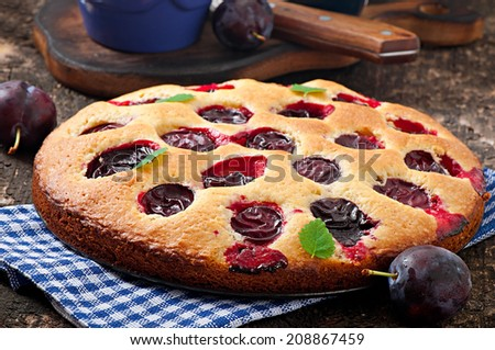 Delicious homemade cake with plums on a wooden background #208867459