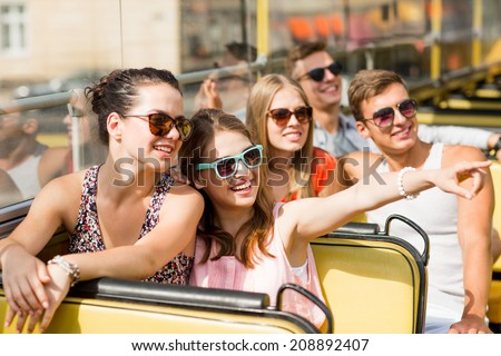 friendship, travel, vacation, summer and people concept - group of smiling friends traveling by tour bus Royalty-Free Stock Photo #208892407