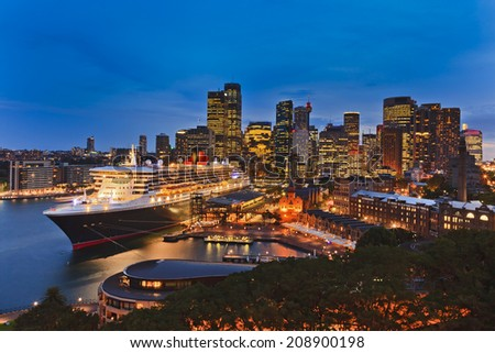 Australia Sydney Circular quay international seaport passenger terminal with docked ocean liner and city CBD in the background illuminated at sunset Royalty-Free Stock Photo #208900198