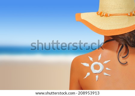 Woman with sun shaped sunscreen on her back #208953913