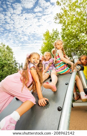 Girl climbs on playground construction and mates #208962142