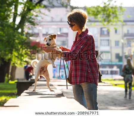 woman walking with a pet in the city park #208967971