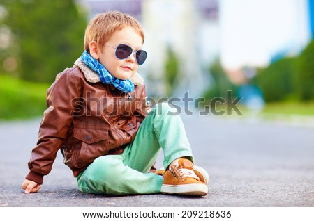 cute stylish boy in leather jacket sitting on the road Royalty-Free Stock Photo #209218636