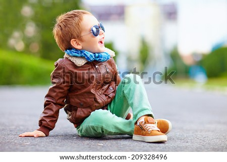 happy boy in leather jacket posing on the ground Royalty-Free Stock Photo #209328496