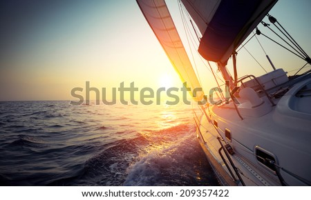 Sail boat gliding in open sea at sunset Royalty-Free Stock Photo #209357422