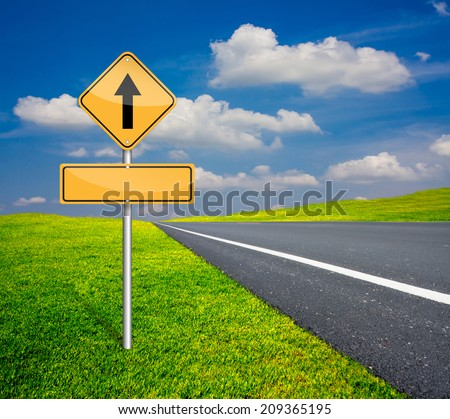 straight traffic sign with blank signs beside asphalt road and blue sky with green meadow #209365195