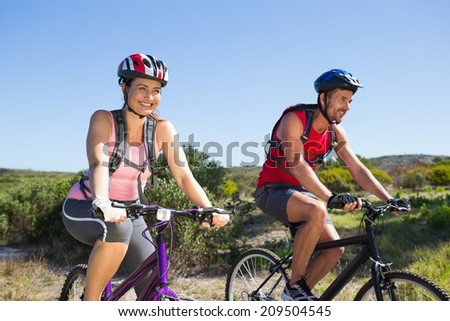 Active couple cycling in the countryside on a sunny day #209504545