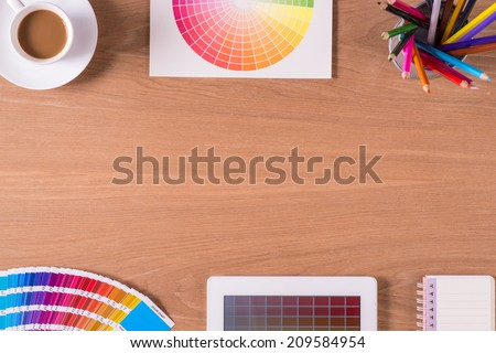 Modern office workplace with digital tablet, notepad, colorful pencils, cup of coffee, and color swatches on a desktop. View from the top