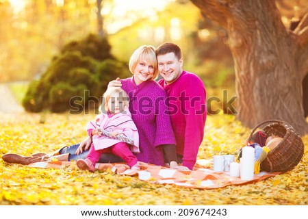 Picture of lovely family in autumn park, young parents with nice adorable kid playing outdoors. Picnic in the autumn park.