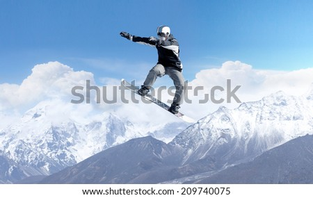 Snowboarder making high jump in clear blue sky #209740075