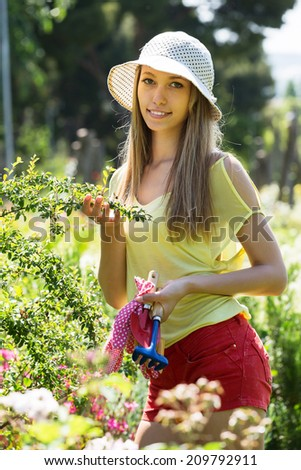 Happy young woman working in the garden in sunny day  #209792911